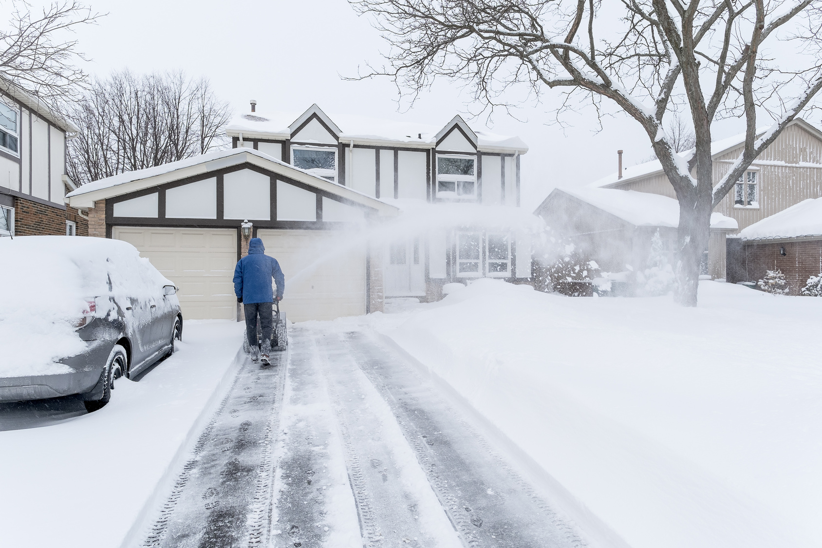 A garage doors man clearing snow with a snow blower for Garage door repair roy utah