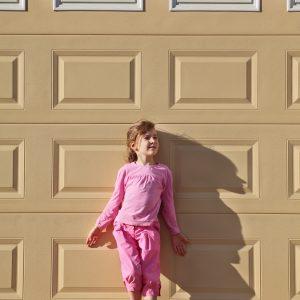 Little girl in front of garage door