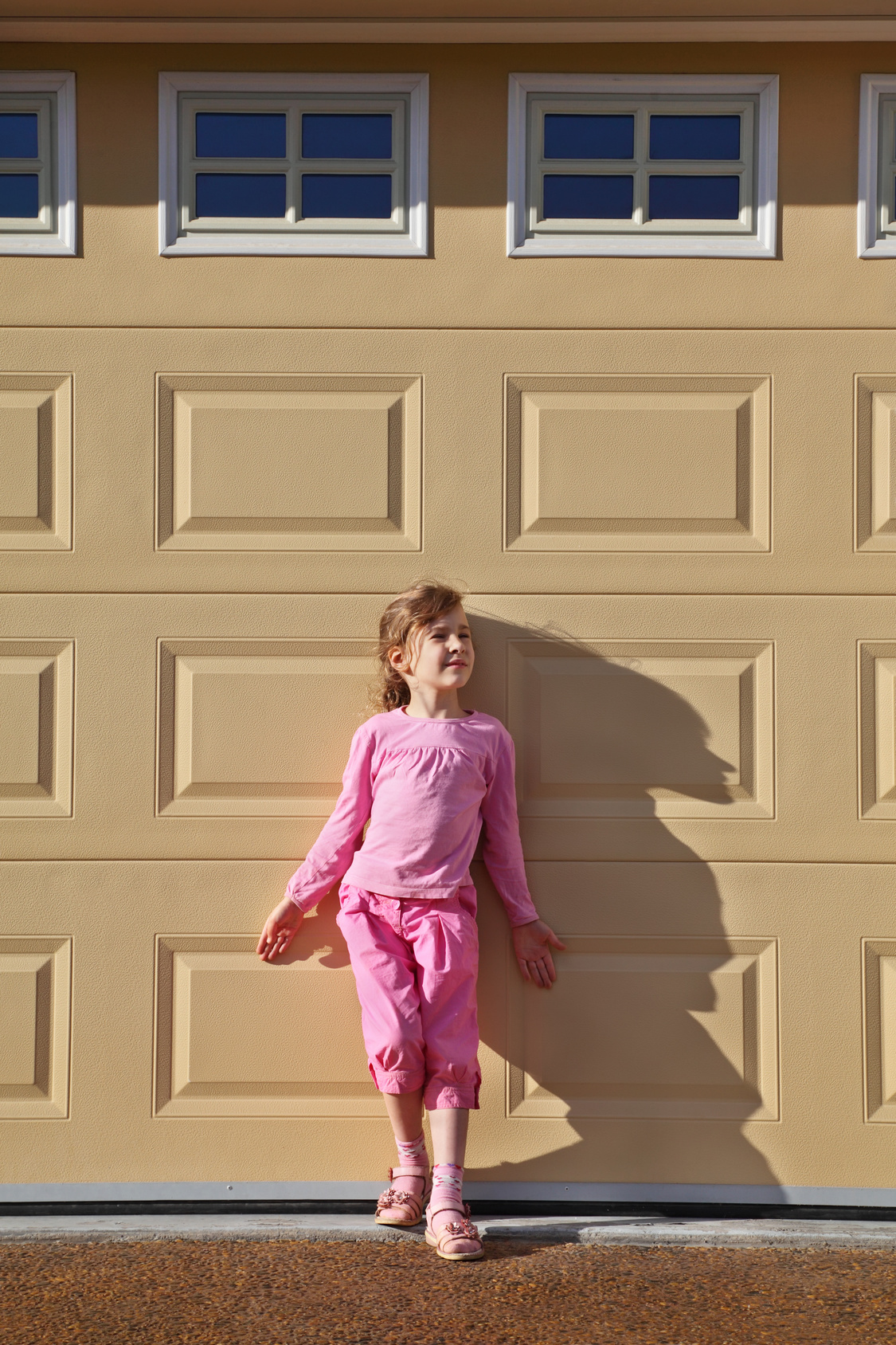 Little girl in front of garage door