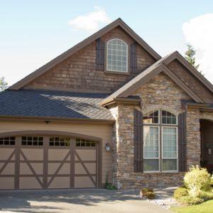A nice garage door sits next to a nice home.