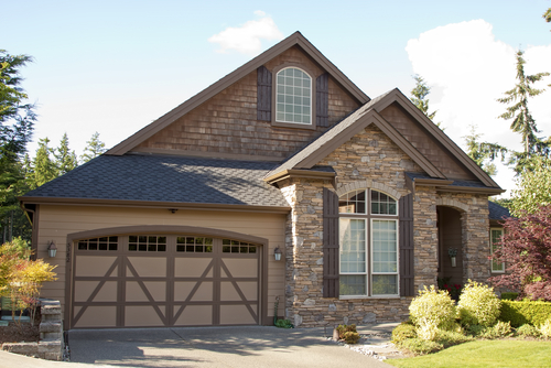 A nice garage door sits next to a nice home.