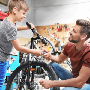 Dad, son fix bike in garage
