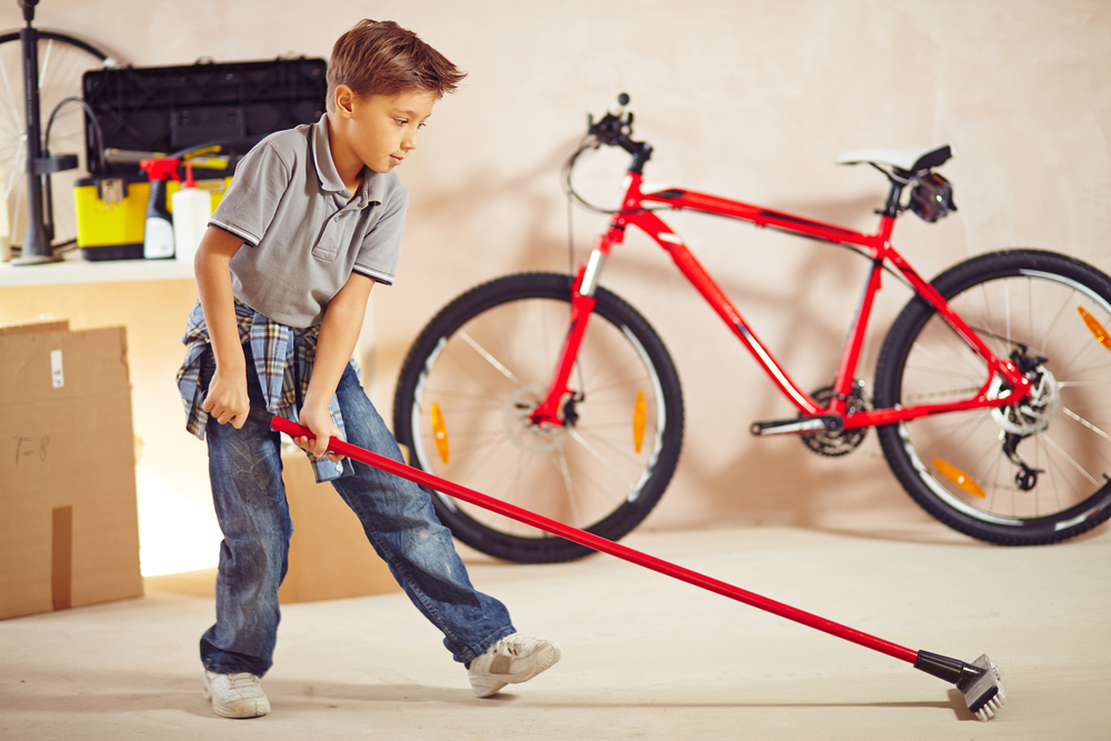 Young Boy Sweeping Garage